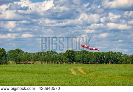 A Windsock In The Form Of A Red And White Fabric Cone Is Fully Deployed On The Airfield Of The Airfi