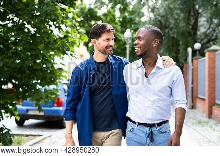 Gay Couple Dating In Jeans. Walking On Street In City