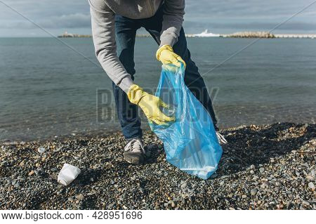 A Man Volunteer Collects Garbage On A Dirty Beach. The Concept Of Waste Recycling, Environmental Cle