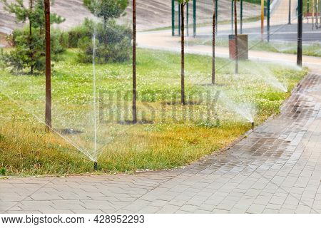 An Automatic Irrigation System Irrigates The Green Lawn In The Young Garden Of The City Park.