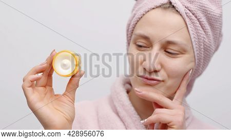 Attractive Girl Holding A Small Jar Of Moisturizing Skin Cream. The Girl Wearing A Head Towel And Ba
