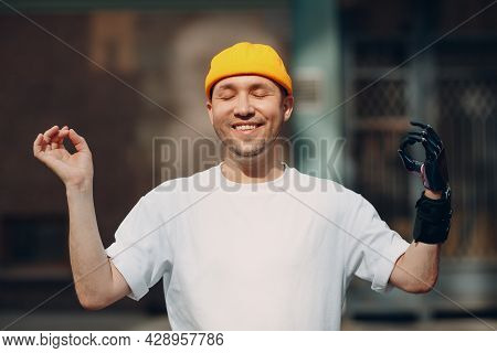Young Disabled Man With Artificial Prosthetic Hand Ok Gesture Mudra Meditate On City Street Outdoor