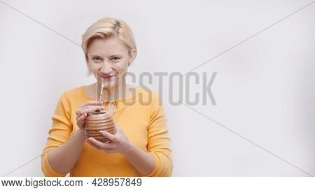 Beautiful Girl Holding A Brown Container Shape Like A Coconut With A Straw. About To Drink With The