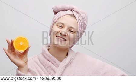 Cheerful Girl Holding Half Orange And Covering Her Eye With The Orange. The Girl Is Wearing A Baby P
