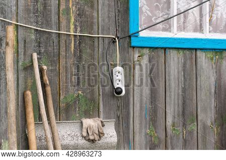An Electric Wire With A Socket Hangs On The Wooden Wall Of The House Near The Window
