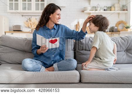 Happy Young Single Mom Parent Touch Kid Hair Thanking For Gift, Smiling Caucasian Mum Sit On Sofa Wi