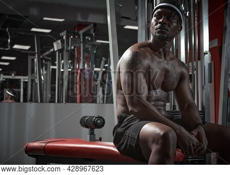 Athletic African American Man With Naked Torso Sitting On Sports Bench During Training In Gym. Sport