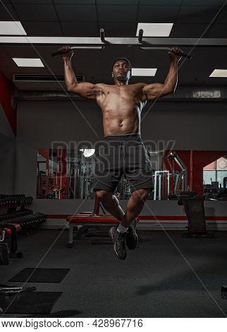 Muscular Athletic African American Guy Doing Chin-ups Or Pull Ups Exercising On Training In Gym