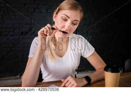 Portrait Of Thoughtful Concentrated Young Adult Caucasian Woman Biting Pen Whilst Reading A Document