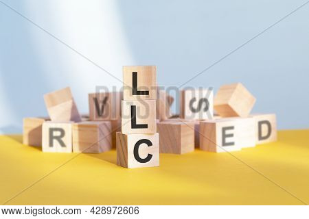 Wooden Cubes With Letters Llc Arranged In A Vertical Pyramid, Yellow Background
