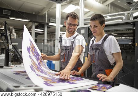 Graphic Engineers Or Workers Checking Imprint Quality In Modern Print Shop.