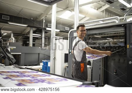 Worker Taking Imprint From Modern Printing Machine To Do Color Matching And Quality Control.