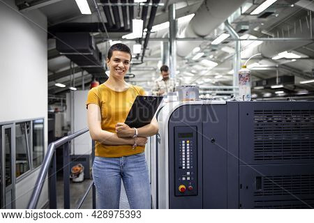Portrait Of Talented Female Designer Standing By Modern Printing Machine In Print Shop.