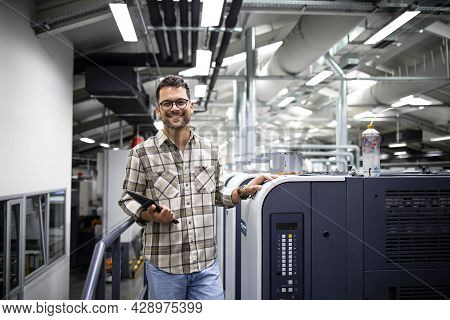 Portrait Of Print Manager Standing By Large Offset Printing Machine In Print Factory.