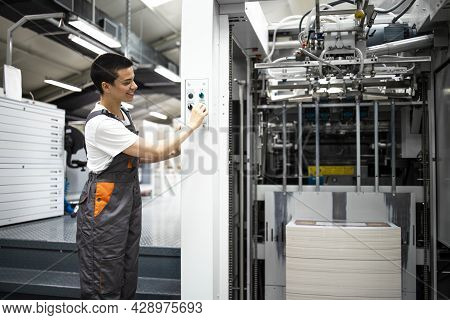 An Experienced Female Print Worker Starting Modern Printing Machine In Print House.