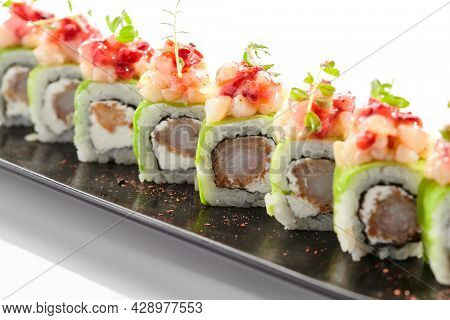 Shrimp Sushi Roll on black slate plate. Luxury maki sushi roll with cream cheese and shrimp inside. Seafood sushi roll topped with spicy scallop. Isolated on white background