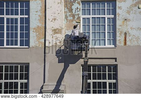 Commercial Painter At The Mobile Crane Truck Cradle Painting A Building Wall That Being Repaired