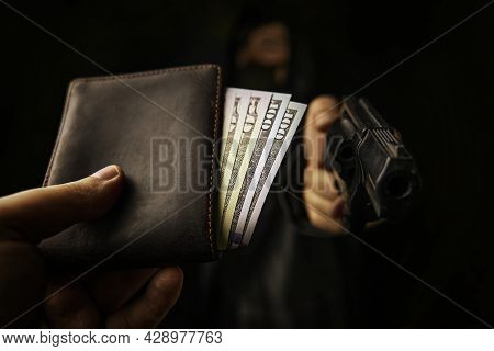 Armed Robbery. Assault On Unarmed Man. Mans Hand Holds Out Wallet Of Money To Robber With Gun. Hundr