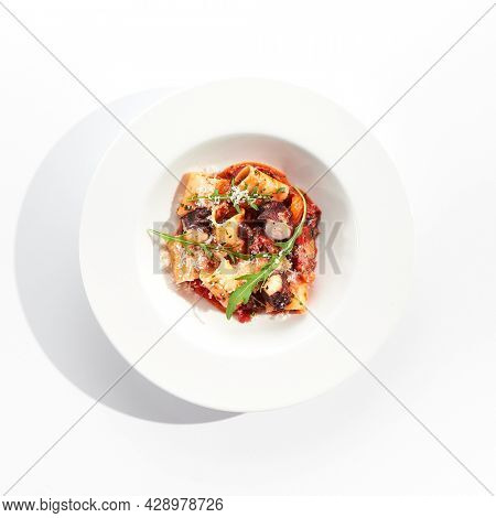 Cannelloni pasta with seafood and Parmesan cheese. Lasagna cannelloni pasta stuffed with tomato sauce and fried octopus. Italian pasta in white plate isolated on white background