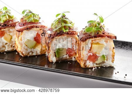 Japanese sushi roll with japanese omelette - tamagoyaki. Sushi roll with avocado and cream cheese inside, topped with fried tuna. Delicious sushi roll with fish topped with sauce and fresh greens
