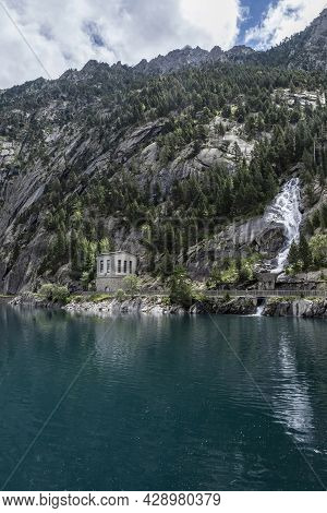Cavallers Reservoir Between High Mountains, A Waterfall And A Building Of The Hydroelectric Power St