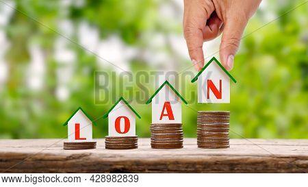 Hand Holding A House Model With Loan Text And A Small House Model On A Pile Of Real Estate Investmen