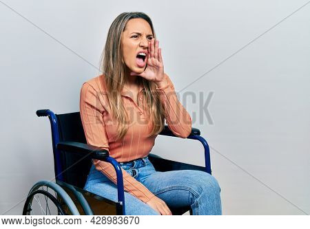 Beautiful hispanic woman sitting on wheelchair shouting and screaming loud to side with hand on mouth. communication concept.