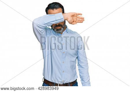 Middle aged man with beard wearing business shirt covering eyes with arm, looking serious and sad. sightless, hiding and rejection concept