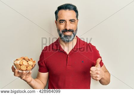 Middle age man with beard and grey hair holding bowl with salty crackers biscuits smiling happy and positive, thumb up doing excellent and approval sign