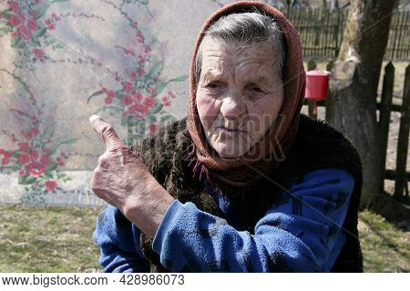 Turiysk, Ukraine - April 03 2009: Old Woman With Kerchief Pointing Forefinger At Spring Time Outdoor