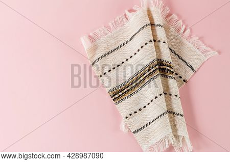 White Napkin With Fringe And Traditional Pattern On A Pink Background. Top View. Copy Space.