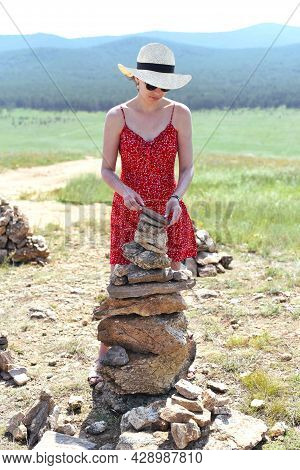 Russian Tourist Building Cairn. Rock Balancing As A Shamanism Religion Symbol In Olkhon Island, Russ