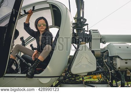 Brunette Tweenager In Mirrored Sunglasses Sitting In Open Helicopter Cockpit