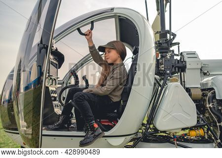 Tween Girl Sitting On Pilot Seat In Modern Helicopter Cockpit