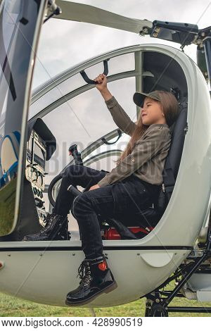 Smiling Preteen Girl Sitting On Pilot Seat In Open Helicopter Cockpit