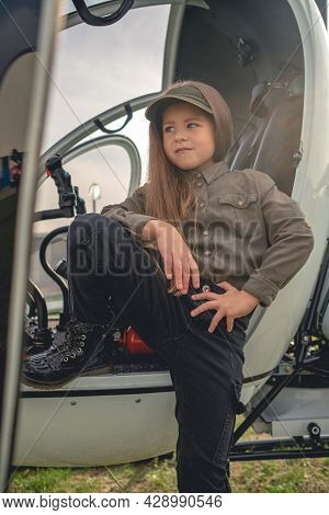 Confident Preteen Girl Standing Near Open Cockpit Of Helicopter