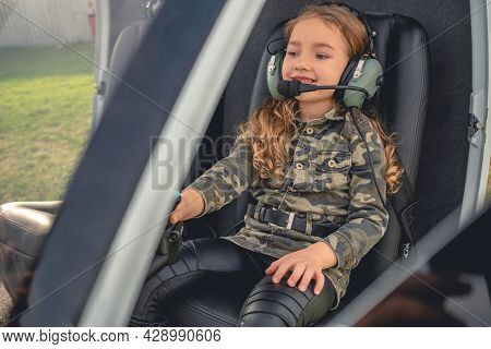 Cheerful Tween Girl In Headset Sitting On Pilot Seat In Helicopter