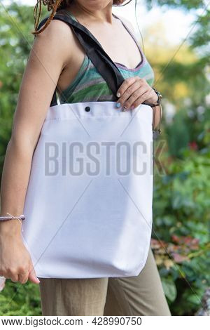 Young woman holding white tote bag, no face, empty place shopper bag mockup