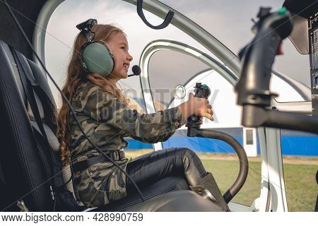 Smiling Tween Girl In Aviator Headset Sitting In Helicopter Cockpit