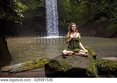 Yoga Lotus Pose. Caucasian Woman Sitting On The Stone, Meditating, Practicing Yoga And Pranayama. Br