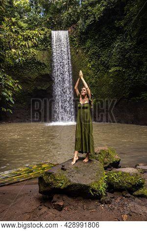 Woman Standing On The Stone Near Tibumana Waterfall In The Jungle. Hands Raised Up In Namaste Mudra.