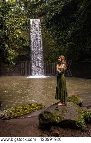 Woman Standing On The Stone Near Tibumana Waterfall In The Jungle. Hands In Namaste Mudra. Caucasian
