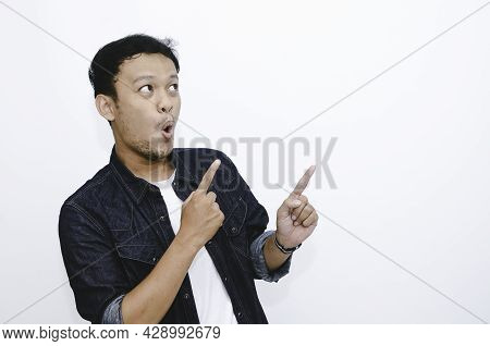 Wow And Shock Face Of Young Asian Man In White Shirt With Hand Point On Above Empty Space.