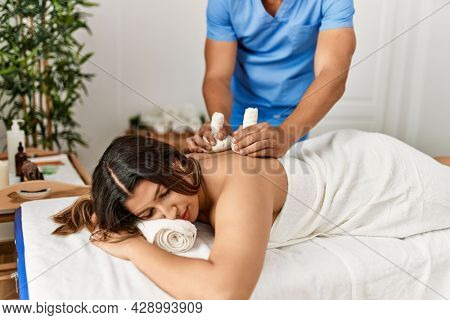 Young woman reciving herbal pouches massage at beauty center.