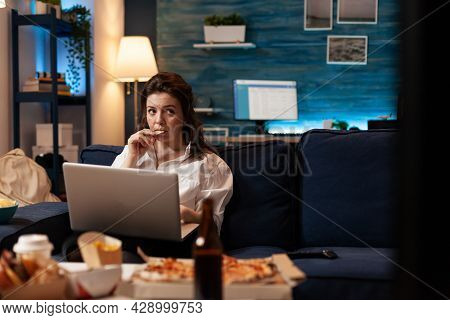 Woman Eating Tasty Snack Working On Laptop Computer While Watching Documentary Movie Series On Telev