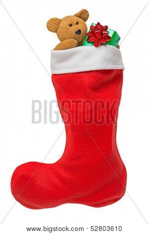 Red Christmas stocking with gifts and handmade teddy bear isolated on white
