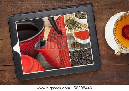 reviewing pictures of tea on a digital tablet, a grunge wood background with a cup of hot tea