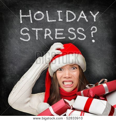 Christmas holiday stress. Stressed woman shopping for gifts holding christmas presents wearing red santa hat looking angry and distressed with funny expression on black chalkboard background.