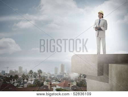 Full length of a male architect with hard hat and clipboard against the sky and cityscape poster