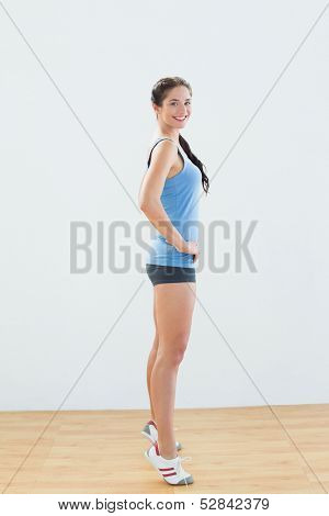 Side view portrait of a smiling slim young woman tip toeing